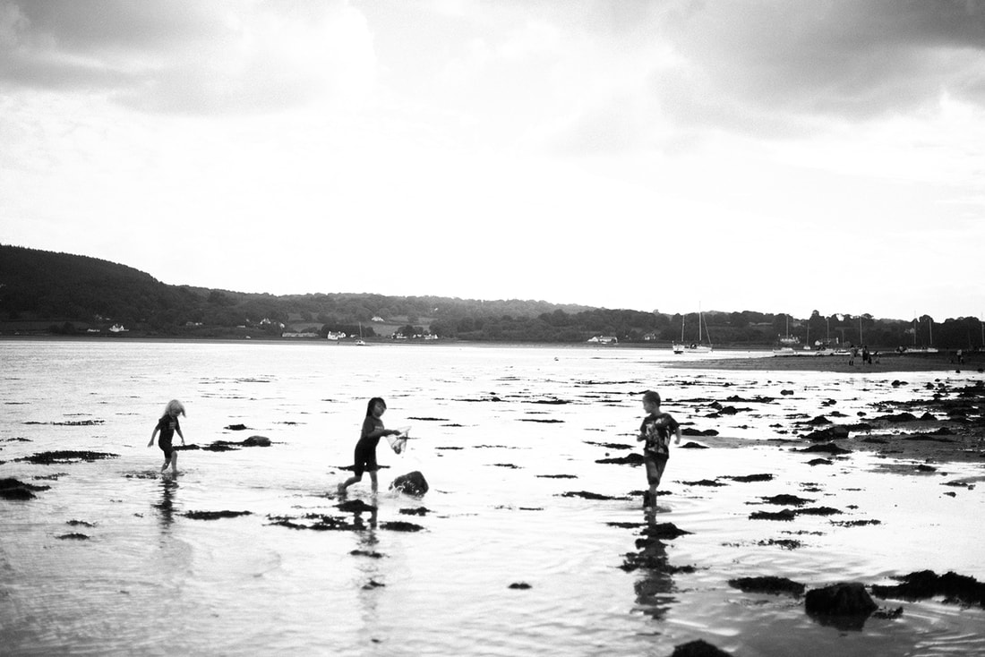 Black and white image of kids running on the beach, taken by a Stockport photographer
