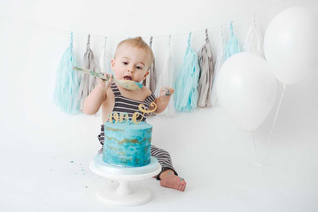 boy licking spoon in cake smash photoshoot