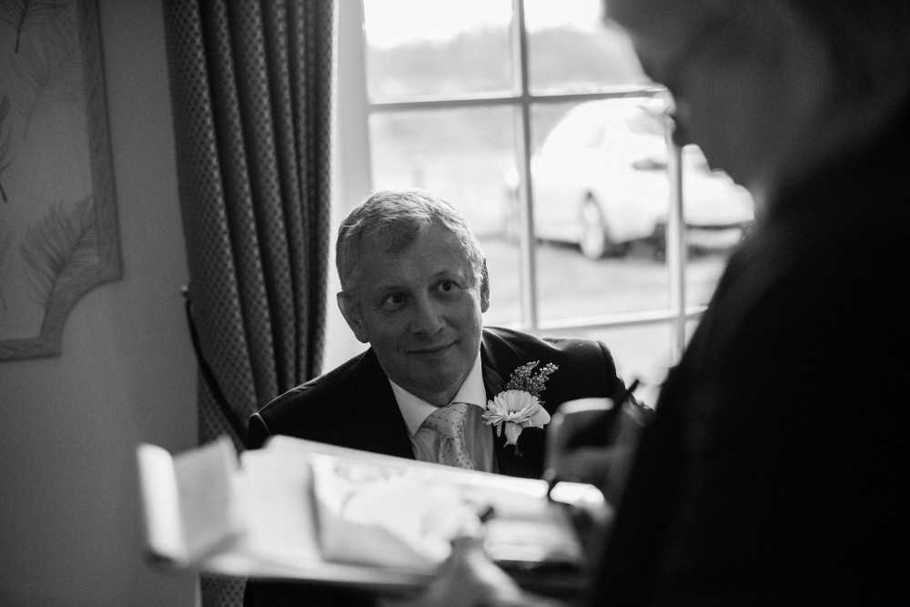 Father of groom speaks to registrar at Deanwater Hotel Wedding Woodford Stockport