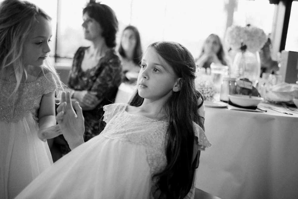 Flower girl leaning on chair at Bramhall Hall Wedding