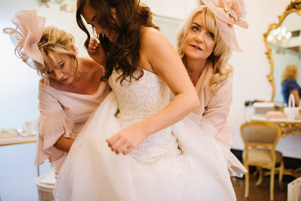 Bride getting into her dress at Colshaw Hall Wedding