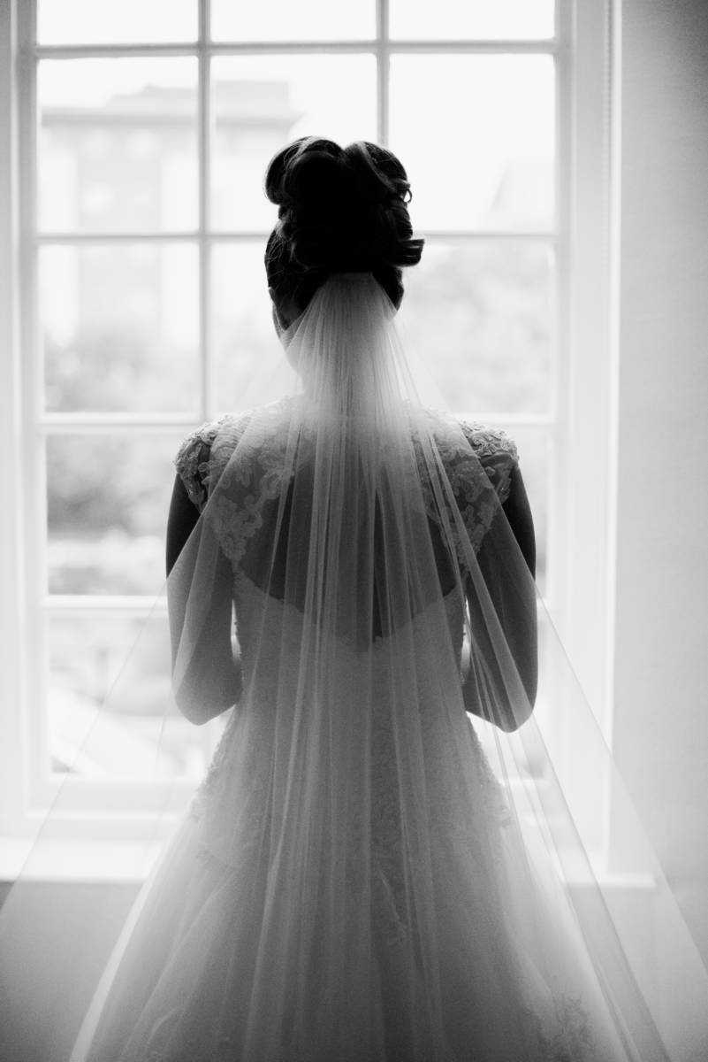 Photograph of Bride looking through big window at Castlefield Rooms Manchester Wedding taken by Stockport photographer